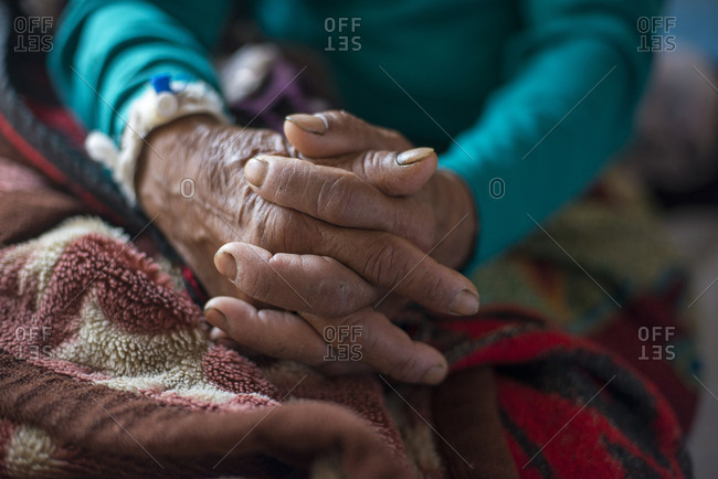 An old lady in a hospital in Nepal clasps her hands together