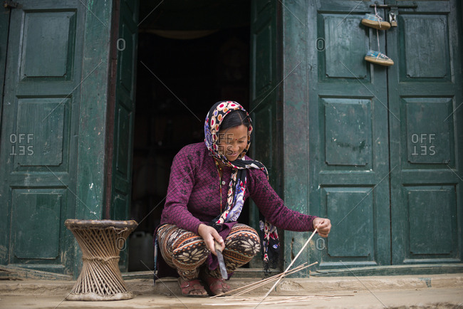 A woman makes a stool from strips of bamboo