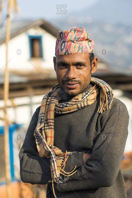 A portrait of a Nepali man wearing a traditional Nepalese hat called a Topi in a small village