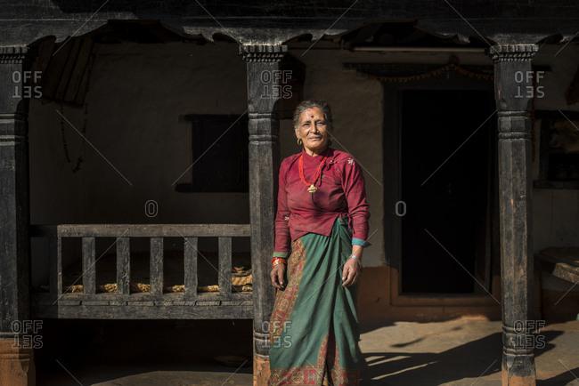 A woman wearing traditional Nepali style dress outside an old house near Diktel