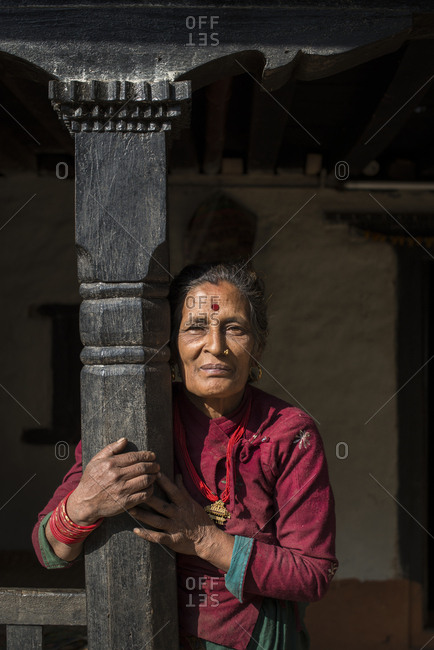 Senior woman wearing traditional Nepali style dress outside an old house near Diktel