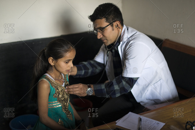 Diktel, Khotang District, Nepal - December 9, 2015: A doctor listens to a young girl's heartbeat with a stethoscope in Diketl hospital in Nepal