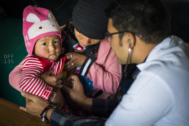 Diktel, Khotang District, Nepal - December 9, 2015: A doctor listens to a baby's heartbeat with a stethoscope in Diketl hospital in Nepal