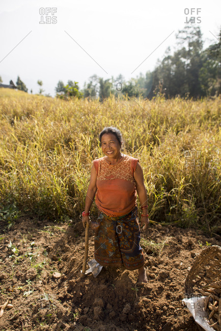 A Nepali woman working in a field holds a spade