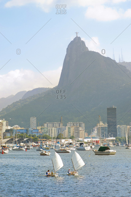 Rio De Janeiro, Brazil - June 15, 2014: Two boys sail in the Botafogo bay, Corcovado mountain in the background