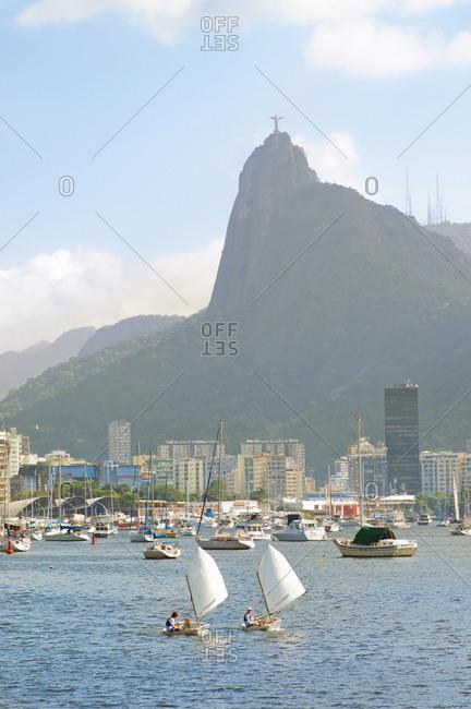 Rio De Janeiro, Brazil - June 15, 2014: Two boys sail in the Botafogo bay, Corcovado mountain in the background