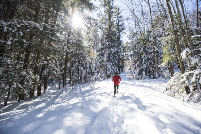Diminishing perspective on man running on trail covered in snow