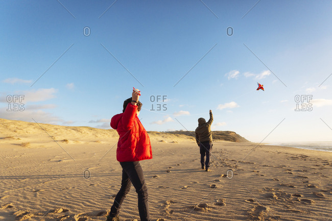 Father and son playing with kite at beach