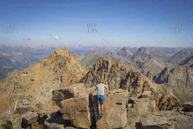 Man Climbing On Top Of The Summit Rock Of Windom Peak