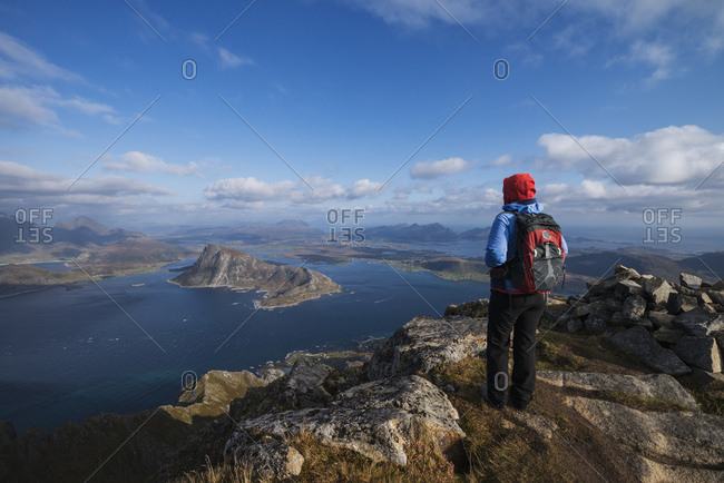 Female hiker enjoys view from the summit of Stornappstind (740m), Lofoten Islands, Norway