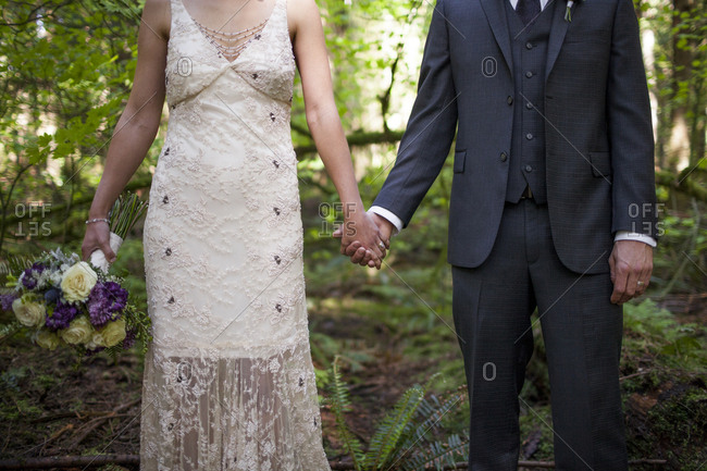 Midsection of newlywed couple holding hands while standing on field in park