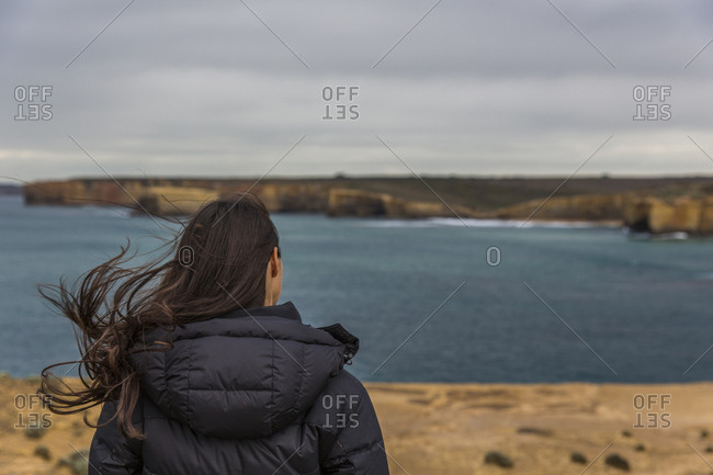 Female looks out at the ocean on a stormy day on the Great Ocean Road