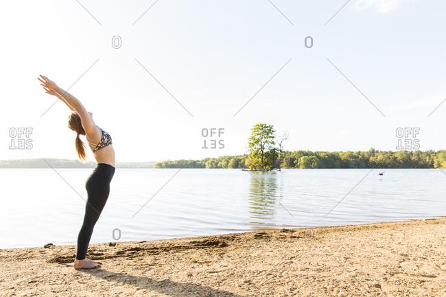 Female yogi does a backwards stretch on the beach