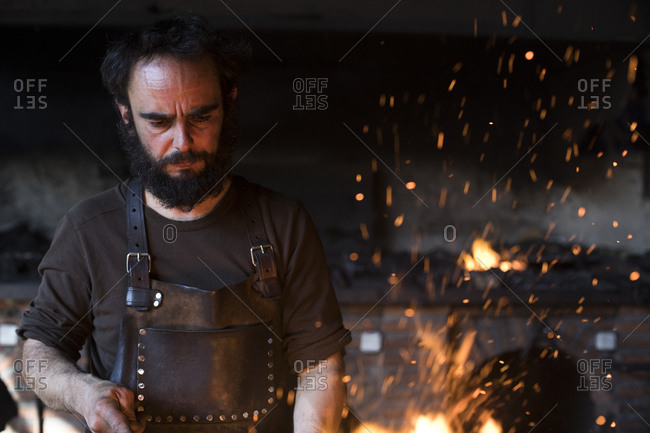 Adult blacksmith working in professional forge