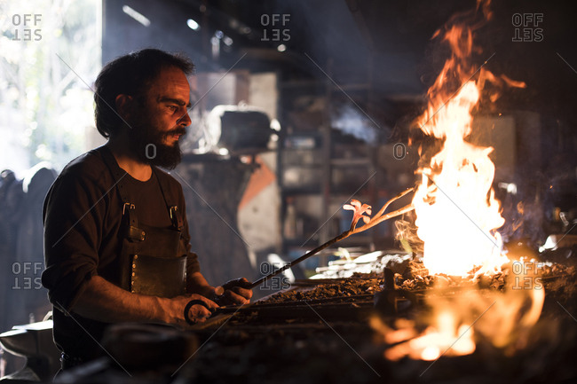 Blacksmith heating iron in fire