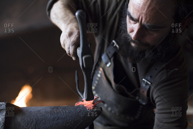 Blacksmith forging a piece of metal in workshop