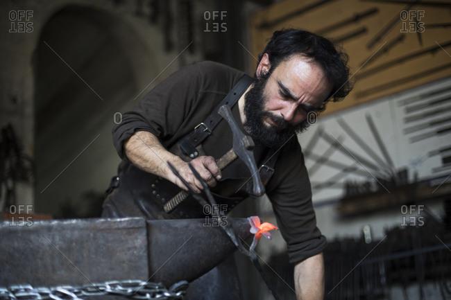 Blacksmith forging metal in workshop