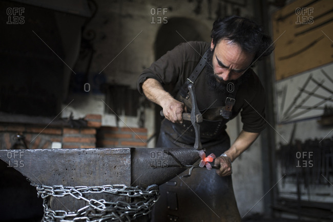 Man in leather apron hitting piece of hot metal with heavy hammer