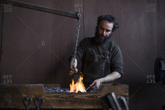 Blacksmith working with fire in workshop