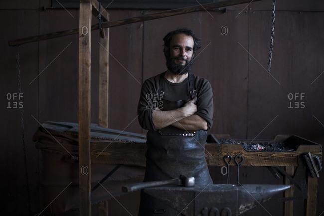 Professional blacksmith near anvil