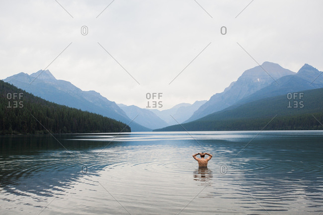 GLACIER NATIONAL PARK, MONTANA, USA. A man faces away from the camera, topless, standing half-submerged in a big lake with mountains in background.