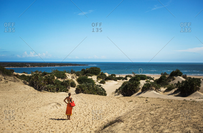 LAMU, INDIAN OCEAN, KENYA, AFRICA. A young woman in a bright orange sarong stands at the top of a vast landscape of dunes and blue water.