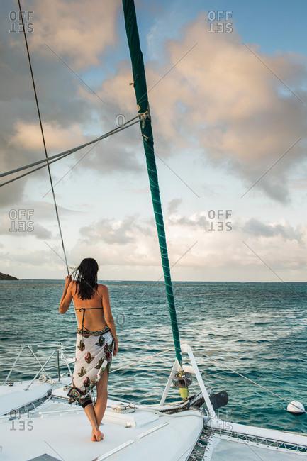 BRITISH VIRGIN ISLANDS, CARIBBEAN. A woman stands on the bow of a catamaran on a calm sea.