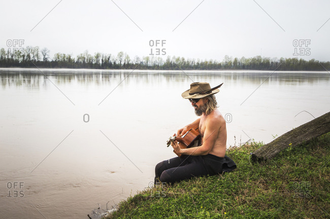 Atchafalaya River, Louisiana, USA. A man with a feather in his cap plays the guitar beside a slow, wide, brown river.