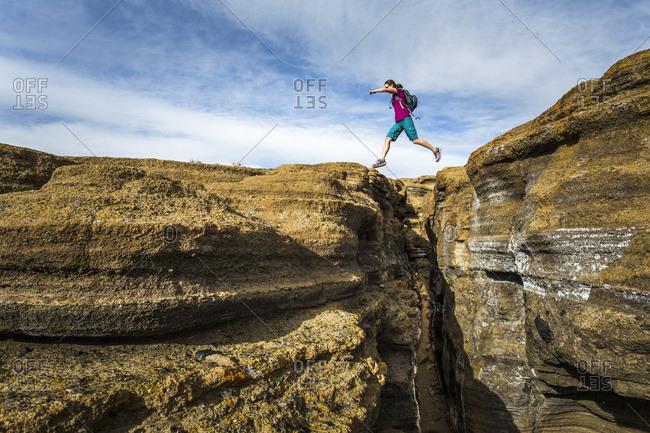 MONO LAKE, CA, USA. A young woman leaps over a deep slot canyon.