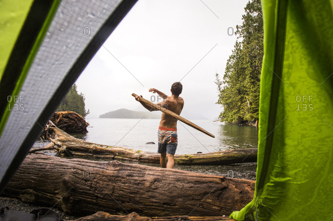 KLEMTU, BRITISH COLUMBIA, CANADA. A shirtless man swings a large stick like a baseball bat on a remote beach, as seen through the opening in a green tent door.
