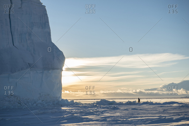 A man walks near a large iceberg in McMurdo Sound in the Southern Ross Sea.