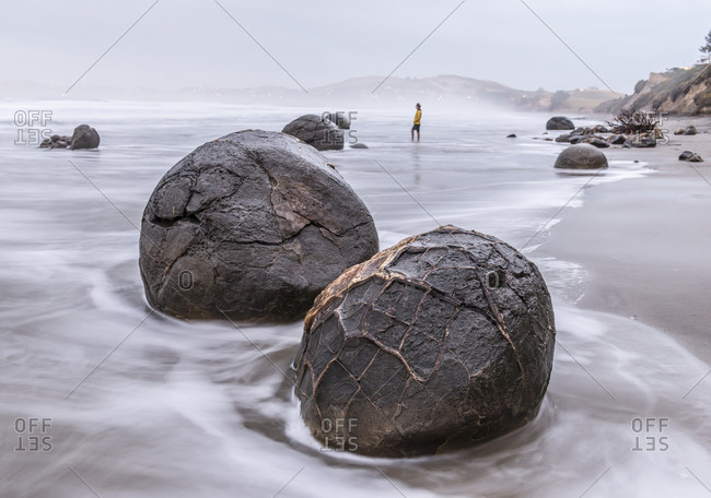 A woman walks on the beach at the Moeraki Boulders, Otago, New Zealand.