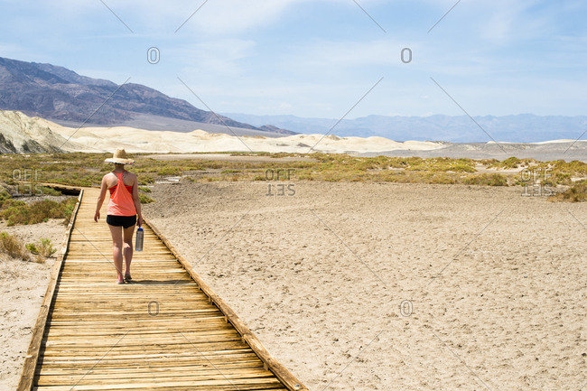 Young female adult walks down walkway in the desert