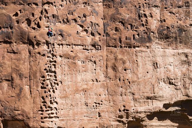 """A woman climbing """"Pocket Rocket"""" outside of Moab, Utah."""