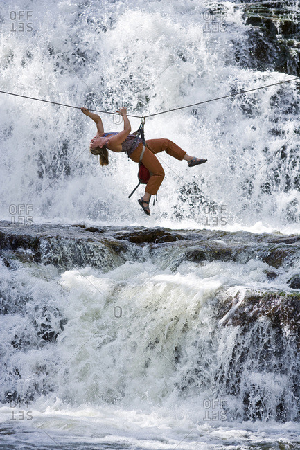 A woman crosses a waterfall using a Tyrolean Traverse on a rope.
