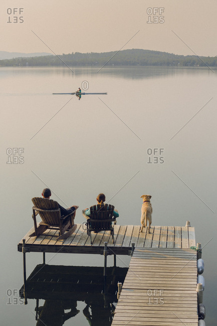 Woman, dog and man relaxing on the end of long lake dock watching a rower.