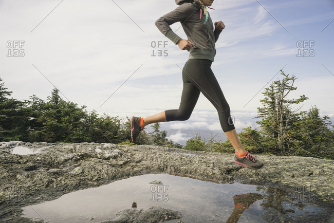 Woman trail running on a rocky ridgeline in New England.