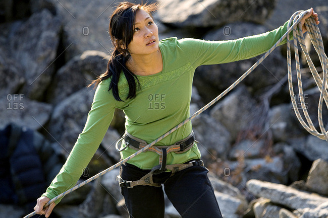 Attractive female climber coiling a rope.