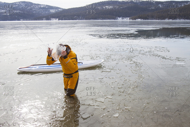 A fit male stand up paddle boarder breaks ice during the winter on Whitefish Lake in Montana.