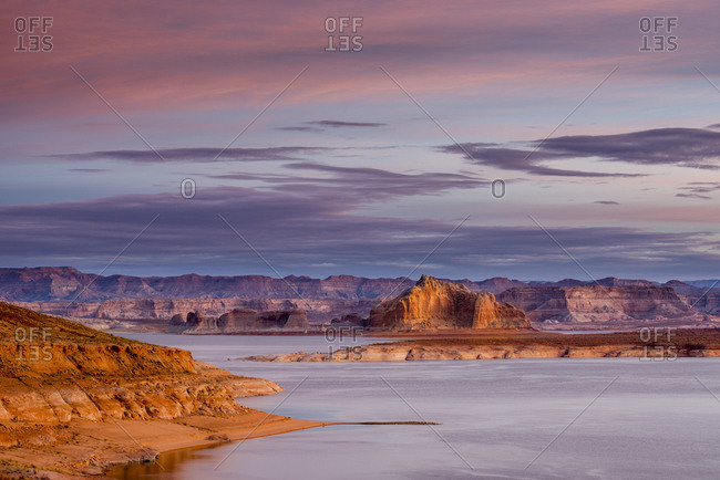 Unique scene of Lake Powell at sunrise with colorful clouds and rocky desert formations.