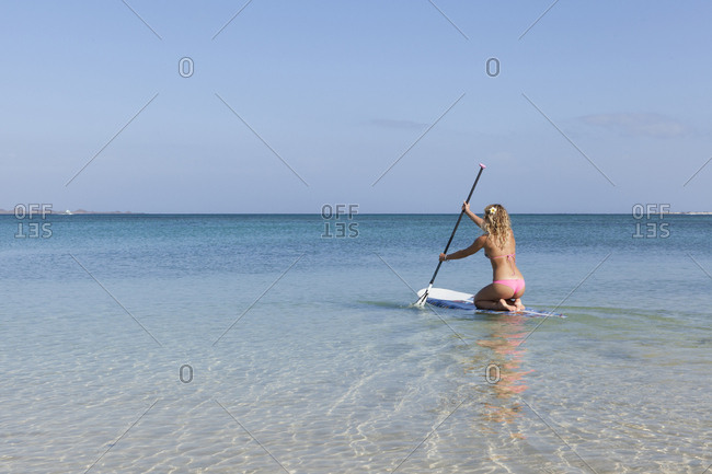 View of one girls in bikini paddling on a stand up paddle board