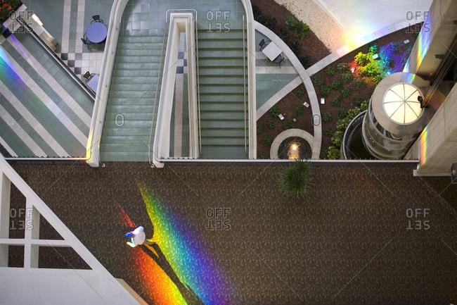 Man walks through a rainbow of spectrum light in a shopping plaza.