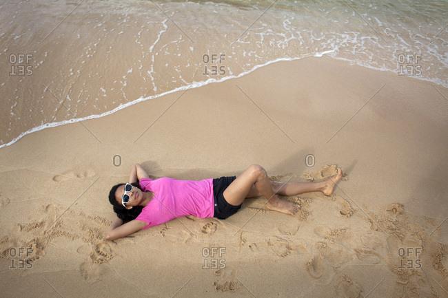 A woman lies down on a beach in Vietnam.