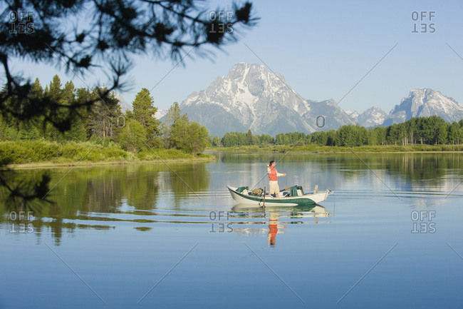 A young man fly fishes from his drift boat.