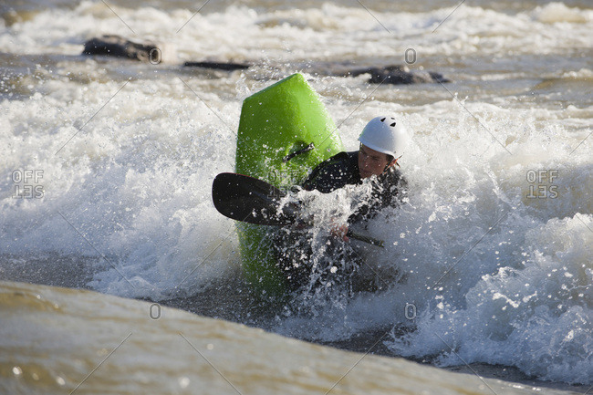 A young male whitewater kayaker playboats on the Clark Fork River, Missoula, Montana.