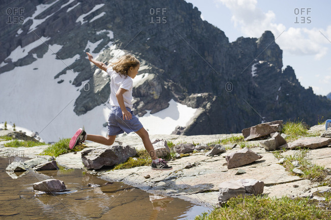 A young girl sails over a pool of water as she hops from rock to rock in Glacier National Park, Montana.