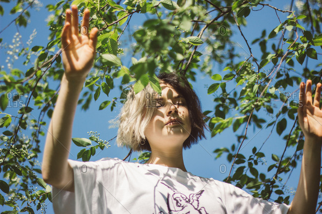 Young girl with closed eyes in summer forest in sunny weather