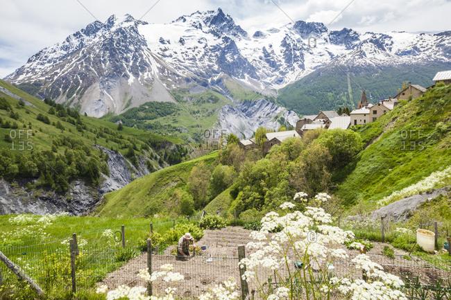 A man cultivates his terraced garden on a steep hillside in Hautes-Alpes, France.