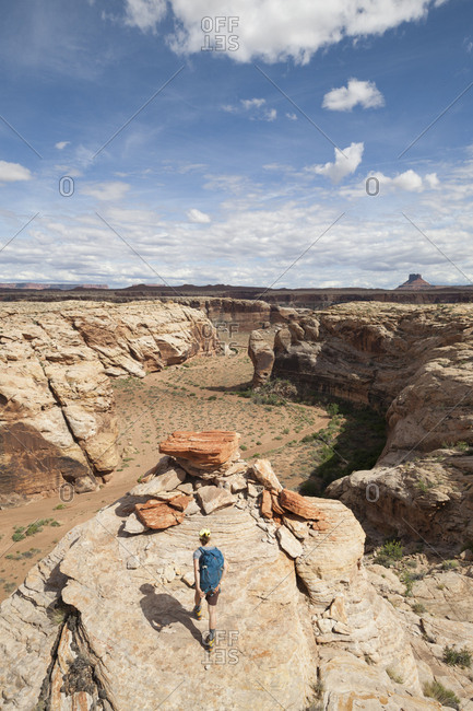 A woman hikes on a bedrock terrace above Anderson Bottom, Canyonlands National Park, Utah.
