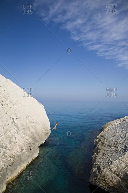 Woman leaps into the ocean, Sardinia, Italy